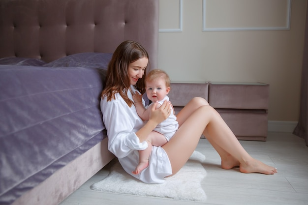 Mooie jonge moeder met baby in haar armen, zittend naast het bed thuis, vrije ruimte