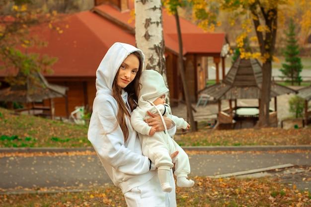 Mooie jonge moeder met babymeisje in de herfst