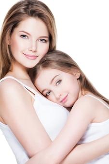Mooie jonge moeder met een kleine dochter 8 jaar omhelzen elkaar in de studio