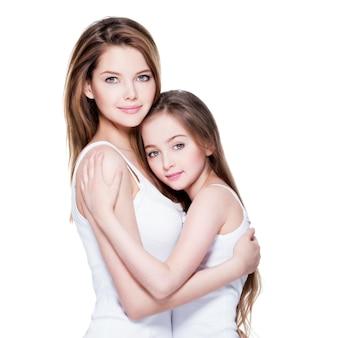 Mooie jonge moeder met een kleine dochter omhelzen elkaar