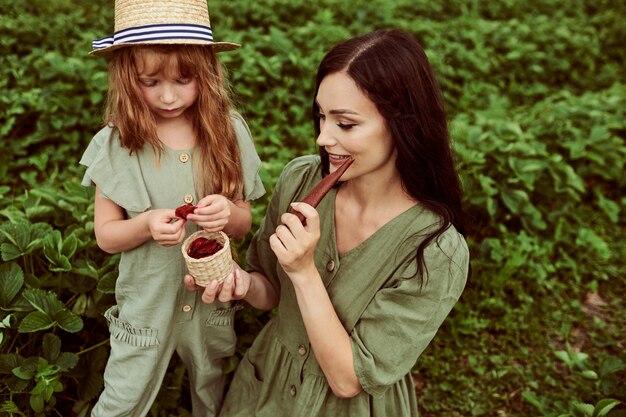 Mooie jonge moeder met haar dochter die pret op een groen gebied met aardbeien heeft