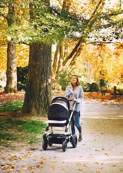 Mooie jonge moeder met kinderwagen wandelen in herfst park