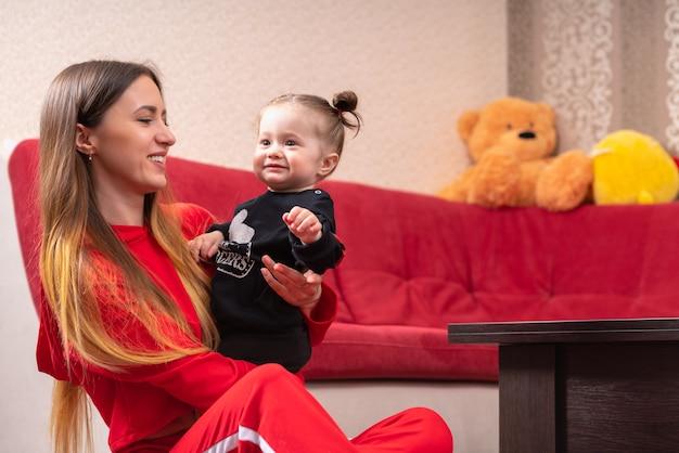 Mooie jonge moeder met lang blond haar, zittend op een vloer in de buurt van rode bank