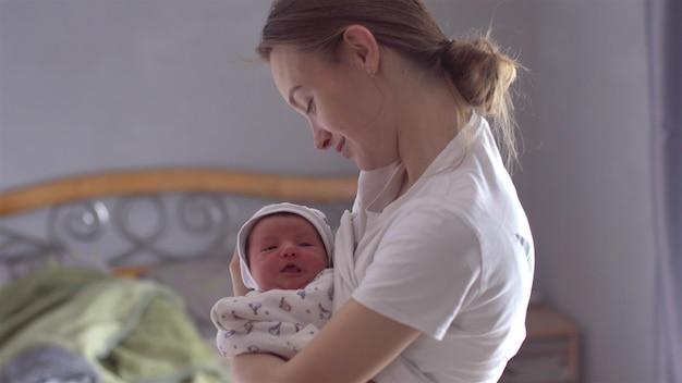 Mooie jonge moeder met pasgeboren baby in haar armen