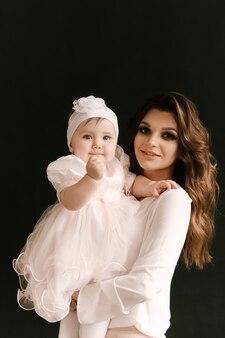 Mooie jonge moeder met schattige lachende babymeisje op zwarte achtergrond