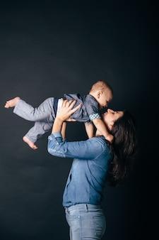 Mooie jonge moeder permanent en houdt haar babyjongen in haar armen voor donkere achtergrond, vrouw speelt met haar schattige kind en lacht. moederdag.