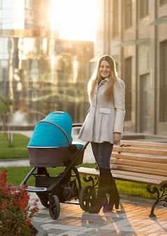 Mooie jonge moeder poseren met kinderwagen op zonnige dag