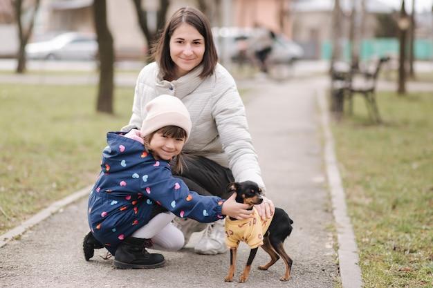 Mooie jonge moeder wandelen met dochter en hondje en gelukkige familie buiten wandelen met huisdier tijdens