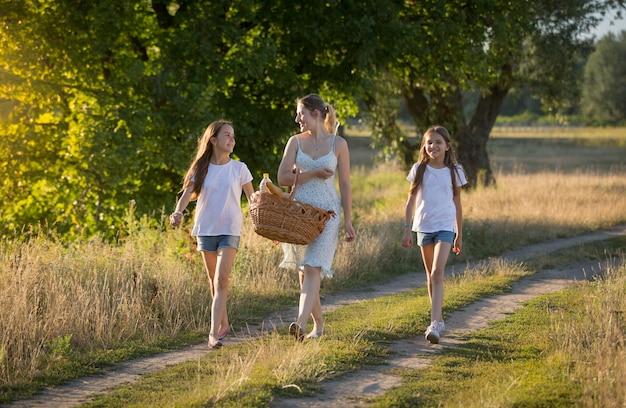 Mooie jonge moeder wandelen met haar dochter in de weide bij zonsondergang