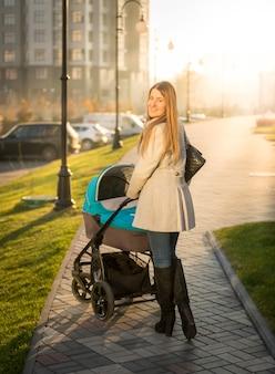 Mooie jonge moeder wandelen met kinderwagen op zonnige straat walking