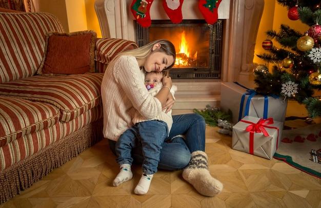Mooie jonge moeder zit met haar zoontje naast de open haard op kerstmis