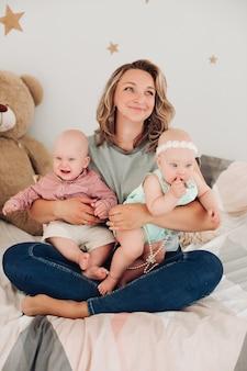 Mooie jonge moeder zit op de grond met haar kinderen en glimlacht
