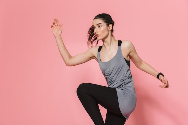 Mooie jonge mooie fitness vrouw die loopt, maakt sportoefeningen geïsoleerd over roze muur Premium Foto