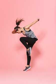Mooie jonge mooie fitness vrouw die loopt, maakt sportoefeningen geïsoleerd over roze muur