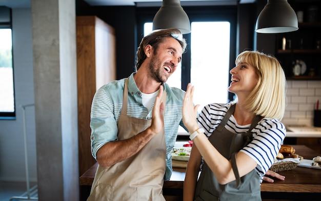 Mooie jonge mooie paar lacht terwijl ze samen koken in de keuken thuis