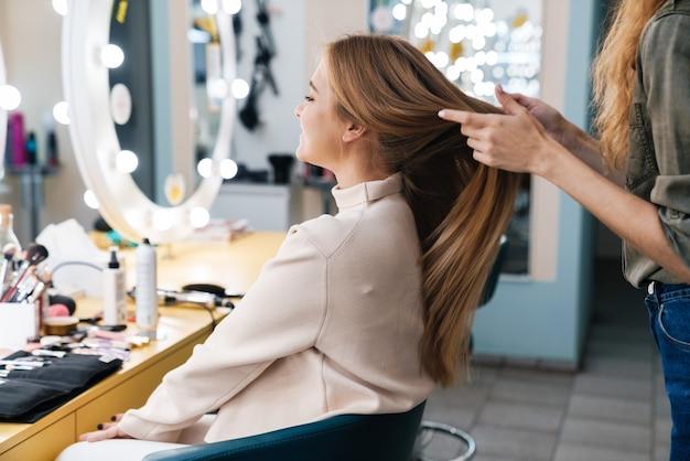 Mooie jonge mooie vrouw klant met kapper in salon.