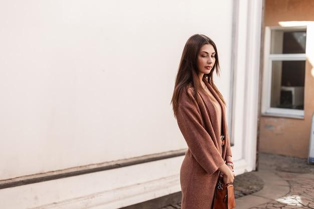 Mooie jonge mooie vrouw mannequin in elegante jas met lederen bruine handtas staande op straat in de stad in de buurt van vintage wit gebouw. europees meisje. vrijetijdskleding voor vrouwen. lente stijl.