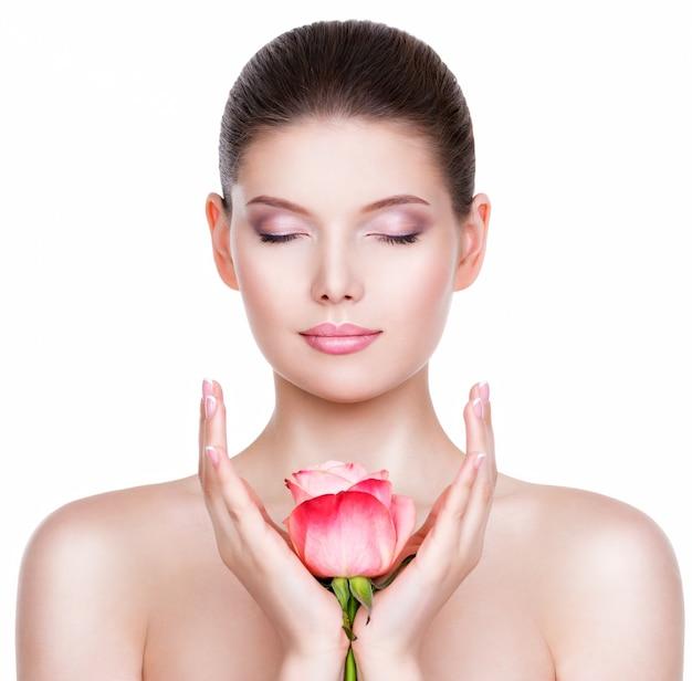 Mooie jonge mooie vrouw met een gezonde huid en roze roos in de buurt van gezicht - geïsoleerd op wit.