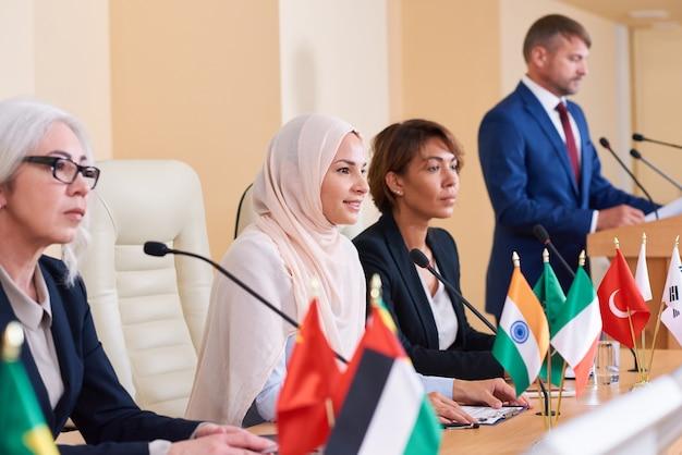 Mooie jonge moslim zakenvrouw luisteren naar publiek na het maken van rapport en het beantwoorden van hun vragen
