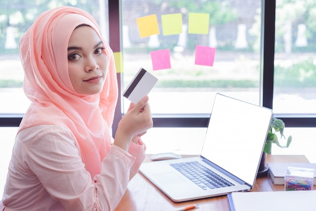 Mooie jonge moslimvrouw die een creditcard met laptop in bureau toont. laptop met leeg scherm
