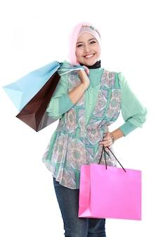 Mooie jonge moslimvrouw die een paar het winkelen zakken houdt