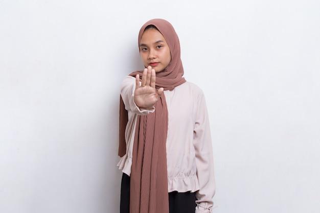 Mooie jonge moslimvrouw met open hand die een stopbord doet met een serieus gezichtsverdedigingsgebaar
