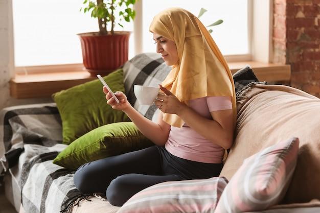 Mooie jonge moslimvrouw thuis tijdens quarantaine en zelfisolatie, met tablet voor selfie of videocall, online lessen