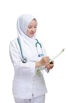 Mooie jonge moslimvrouw verpleegster of arts met klembord geïsoleerd op een witte achtergrond