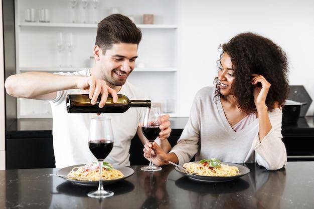 Mooie jonge multi-etnisch paar met een romantisch diner thuis, rode wijn drinken en pasta eten, gieten