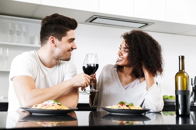 Mooie jonge multi-etnisch paar met een romantisch diner thuis, rode wijn drinken en pasta eten, roosteren