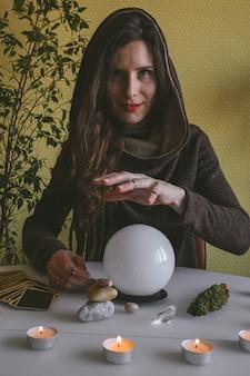 Mooie jonge mysterieuze vrouw in een hoodie houdt haar handen over een kristallen bol