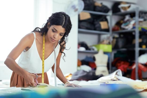 Mooie jonge naaister die zijden stof snijdt voor nieuwe jurk
