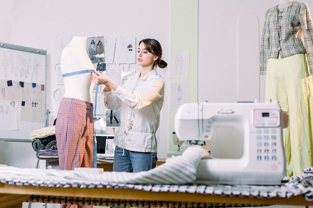 Mooie jonge naaister in de werkkamer. fashion design mannequin meting concept.