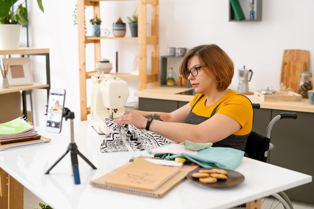 Mooie jonge naaister zittend in een rolstoel door bureau voor smartphonecamera tijdens masterclass voor haar online publiek