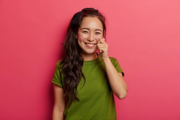 Mooie jonge natuurlijke brunette meisje raakt wang zachtjes, heeft een gezonde huid, vormt mini hart met vingers geïsoleerd op levendige roze achtergrond.