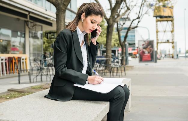 Mooie jonge onderneemster die op omslag met pen schrijft terwijl het spreken op mobiele telefoon