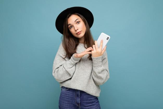 Mooie jonge ontevreden brunette vrouw met zwarte hoed en grijze trui met smartphone kijken naar camera geïsoleerd op de achtergrond vragen. kopieer ruimte