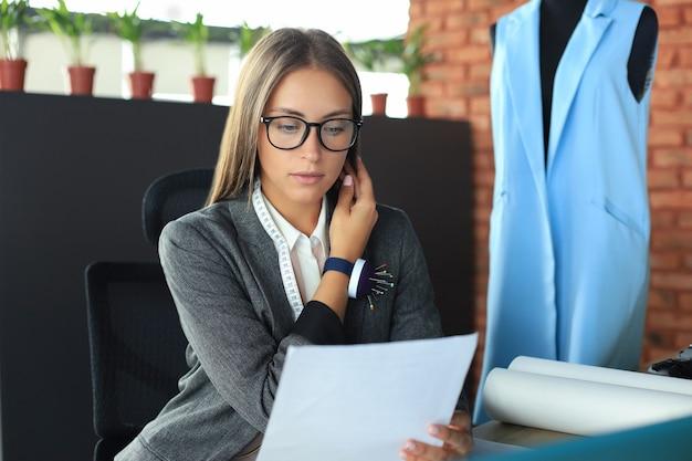 Mooie jonge ontwerper die op slimme telefoon praat terwijl hij aan het bureau zit in haar atelier.
