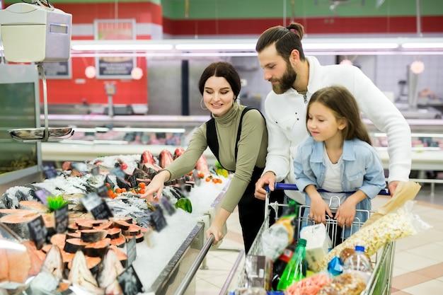Mooie jonge ouders en hun schattige dochtertje glimlachen bij het kiezen van vis in de supermarkt