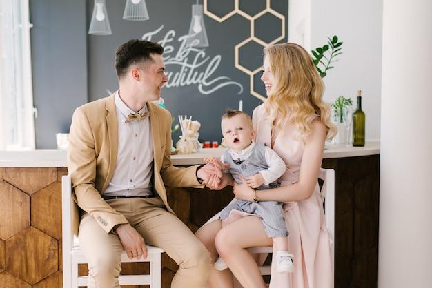 Mooie jonge ouders glimlachen met hun eenjarig kind thuis in een prachtig interieur in pastelkleuren. familie-look. gelukkig verjaardagsfeestje