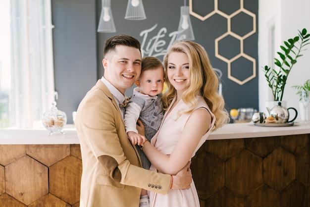 Mooie jonge ouders glimlachen thuis met hun eenjarig kind