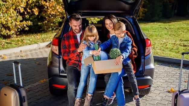 Mooie jonge ouders met hun schattige kinderen zitten in de kofferbak en houden een kartonnen doos met planten en andere dingen thuis tijdens de verhuizing naar een nieuw appartement.