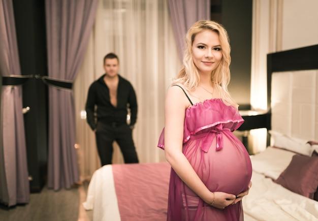 Mooie jonge paar charmante man raakt de buik van zijn mooie zwangere vrouw