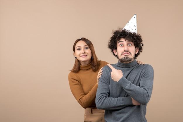 Mooie jonge paar dragen nieuwjaar hoed boos meisje kijken naar iets staande achter boos man haar wijzend op grijs