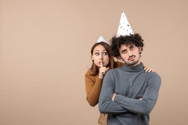 Mooie jonge paar dragen nieuwjaar hoed meisje stilte gebaar maken staande achter man op grijs