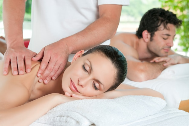 Mooie jonge paar genieten samen van een massage in het kuuroord