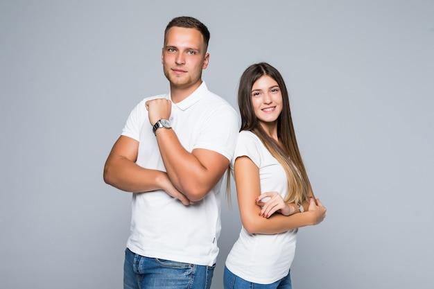 Mooie jonge paar in casual kleding geïsoleerd op lichtgrijze achtergrond gekleed in witte t-shirts