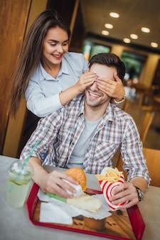 Mooie jonge paar in het moderne fastfoodrestaurant plezier