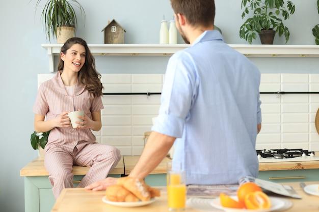 Mooie jonge paar in pyjama's kijken elkaar aan en glimlachen tijdens het koken in de keuken thuis.