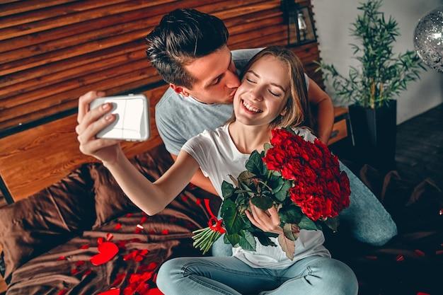 Mooie jonge paar in slaapkamer. jonge vrouw neemt selfie terwijl knappe man haar kust. het vieren van sint-valentijnsdag.